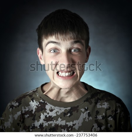Vignetting Photo of Angry Teenager on the Dark Background - stock photo