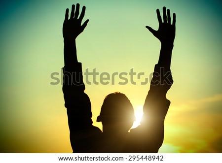 Vignetting Photo of Man Praying on the Evening Sky Background - stock photo