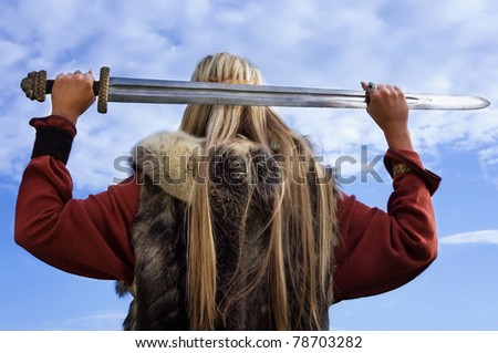 Viking girl with sword on a blue sky background