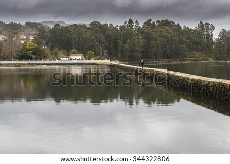 VILABOA, SPAIN - FEBRUARY 15, 2015: A group of people walking on a stone bridge over the sea in a cove. - stock photo