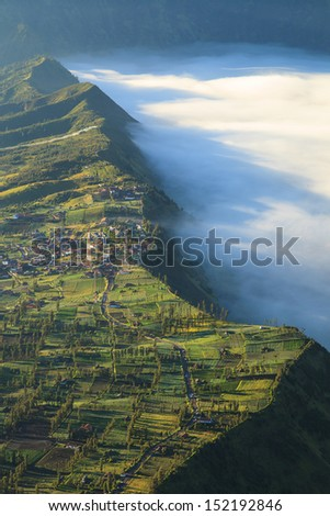 Village and Cliff at Bromo Volcano Mountain in Tengger Semeru National Park at sunrise, East Java, Indonesia - stock photo
