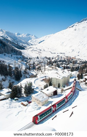 Village Andermatt in winter from above with train passing through, Switzerland - stock photo