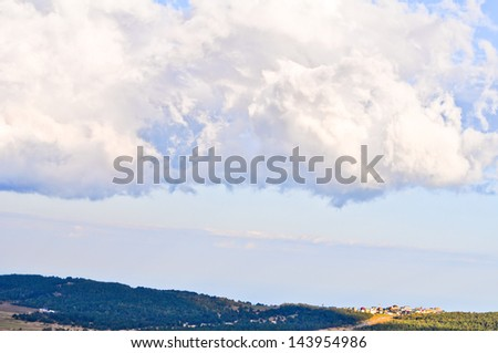 Village from distance under the huge clouds - stock photo
