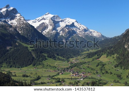 Village Gsteig bei Gstaad and snow capped mountain named Oldenhorn - stock photo