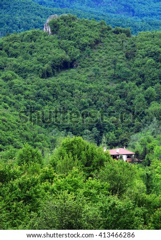 Village house and rock in Balkan mountains - stock photo