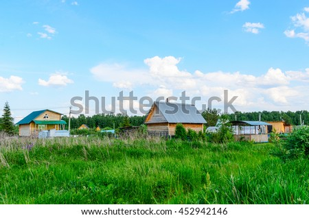 Village house in a field under blue sky with clouds.
