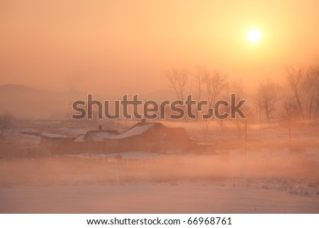 village houses in the background of a beautiful winter sunrise - stock photo