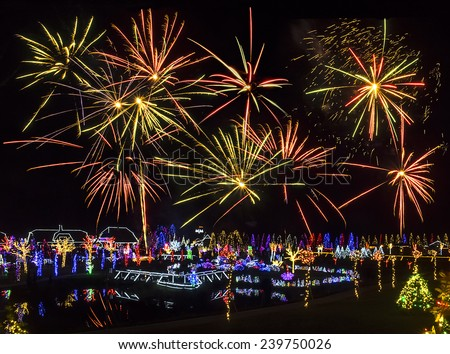 Village illuminated with Christmas lights under fireworks   - stock photo