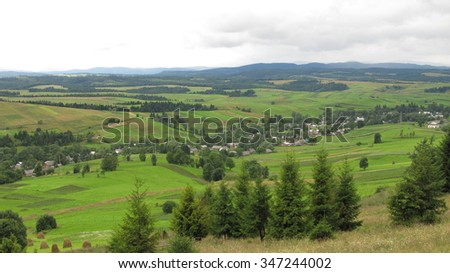 Village in the Carpathian mountains amazing Ukraine. Time of year - summer. Green grass and vegetation. Wooden huts. Cloudy weather. - stock photo