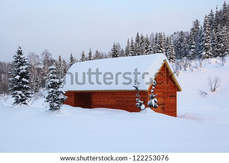 Village in the snow-covered fir forest - stock photo