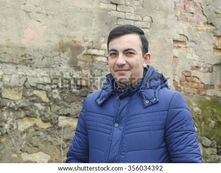 village man stands in front of a stone wall in the jacket