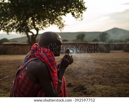VILLAGE MASAI MARA, KENYA - AUGUST 10, 2013. Young Masai warrior showing how they make fire in a traditional way to guests visiting their village in the Masai Mara National Park in Kenya - stock photo