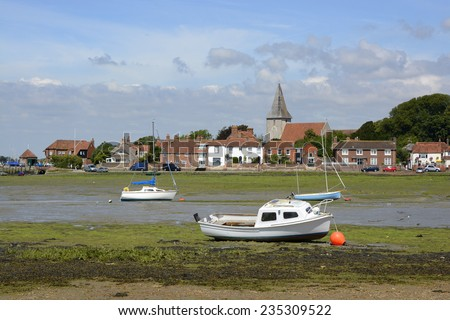 Village of Bosham in Chichester Harbour. West Sussex. England. Low tide with seaweed and beached boats. People in distance