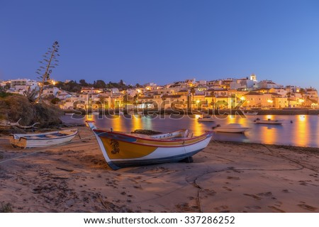 Village of fishermen, Ferragudo yellow lights lanterns. Traditional boat in the foreground.