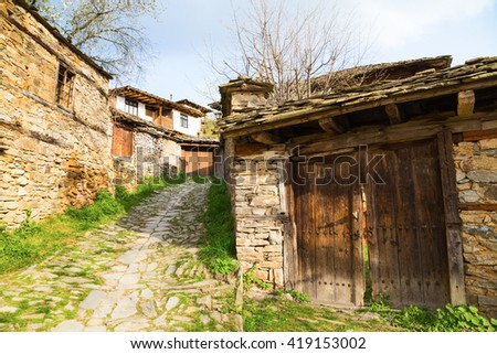Village of Leshten, Bulgaria. Entrance driveway to a rustic stone house with old outbuildings with weathered wooden doors and the house in the background. - stock photo