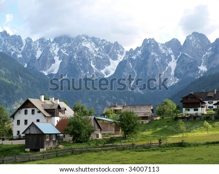 Village on the meadow with snowy peaks in the background. - stock photo