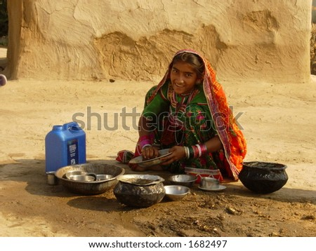 village scene in india, a young girl washing utensils - stock photo