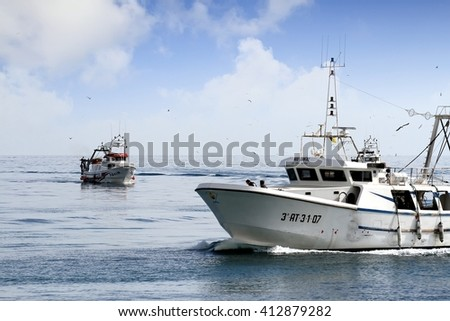 VILLAJOYOSA PORT, SPAIN - MARCH 28. It comes time to sell the fish caught. Trawlers of La Vila harbor are entering to their moorings on March 28, 2016 in Alicante.