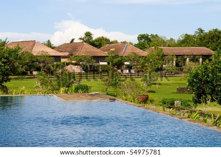 Villas and swimming pool in green field of India - stock photo
