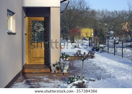 VILNIUS, LITHUANIA - JANUARY 02, 2016: Christmas  wreath on a door of the rural house. Holidays came to an end. In the village snow a frost and silence.