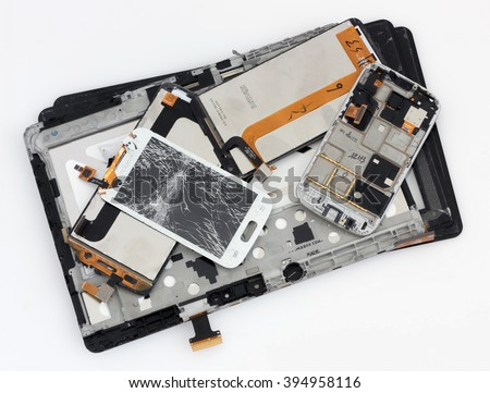 VILNIUS, LITHUANIA - MARCH 23, 2016:  Broken spare parts from  Samsung  brand smart phones and tablets  lie on table in repair service center. In 2014 Samsung sold more than 80 million phones - stock photo