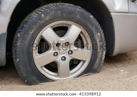 VILNIUS, LITHUANIA - MARCH  03, 2016: The punctured lowered wheel of the American car Dodge on rural sandy Lithuanian roads. Lithuania needs all-terrain vehicles