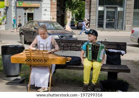 VILNIUS, LITHUANIA - MAY 18: unidentified young street music festival participants girl with baltic psaltery and boy with accordion on the bench on May 18, 2013 in Vilnius.  - stock photo