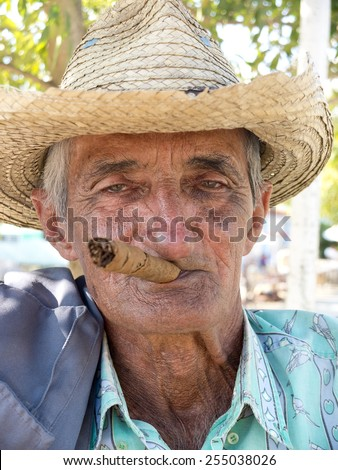 VINALES, CUBA - DECEMBER 16: an old man wearing a straw hat is smoking a cuban cigar outdoors,on december 16, 2014, in Vinales, Cuba  - stock photo