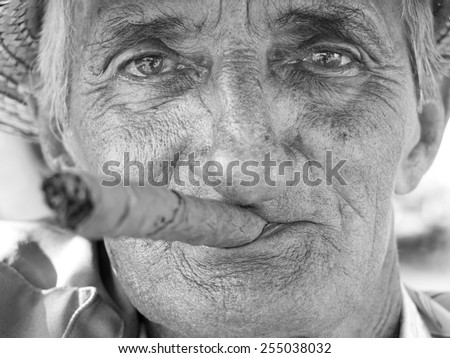 VINALES, CUBA - DECEMBER 16: portrait of an old man wearing a straw hat and smoking a cuban cigar outdoors,on december 16, 2014, in Vinales, Cuba  - stock photo