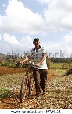 VINALES, CUBA - MARCH 20: Man walks with old rusty bike in Cuban countryside in Vinales on March 20, 2009. Most Cubans live way below established poverty lines, the issue is biggest in rural areas.