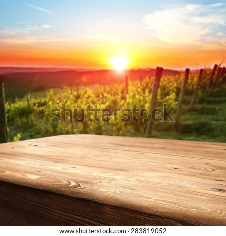 vineyard at sunset in the Chianti region in Italy and table of wood space  - stock photo