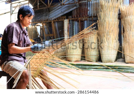 Vinh Long city, Vietnam - 06 May 02, 2015: Unknown, An Asian man weaving handicraft basket from bamboo. The fruit trader on floating market in the Mekong Delta will need the baskets like these