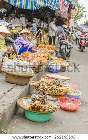 VINH LONG, VIETNAM, JANUARY 3, 2013: Local women sell dried fish and seafood on stalls along the street in Vinh Long market