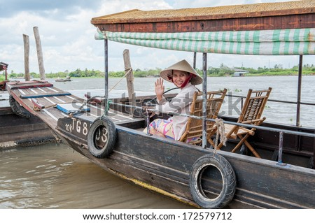 VINH LONG, VIETNAM - MARCH 7: Vietnamese woman sits in a traditional boat on March 7, 2009 in the Mekong delta near Vinh Long. The Mekong river is a major route for transportation in Southeast Asia.