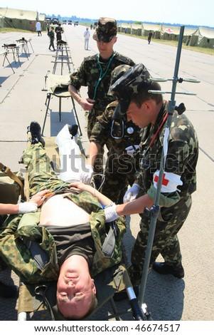 VINNYTSYA, UKRAINE - JUNE 10, 2008: surgeons in military mobile hospital during a medical military trainings on June 10, 2008 in Vinnytsya, Ukraine - stock photo