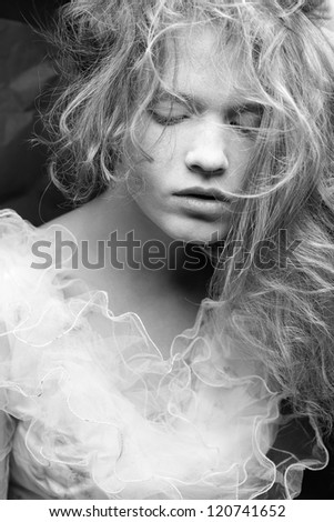 Vintage a-la french princess portrait of a beautiful blond girl. Black and white studio shot. - stock photo