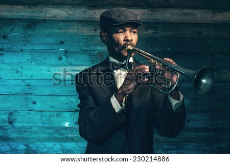 Vintage african american senior jazz musician with trumpet in front of old wooden wall. Wearing black suit and cap. - stock photo