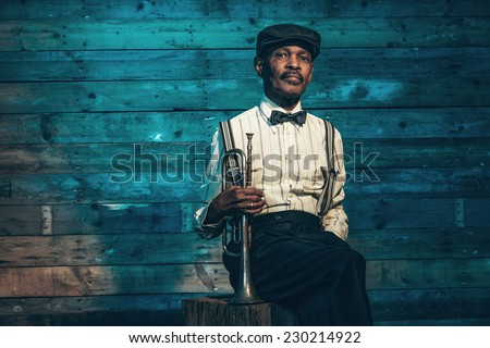 Vintage african american senior jazz musician with trumpet in front of old wooden wall. Wearing suit and cap. - stock photo