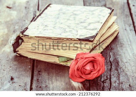 vintage aged closed book on wood desk with rose - stock photo