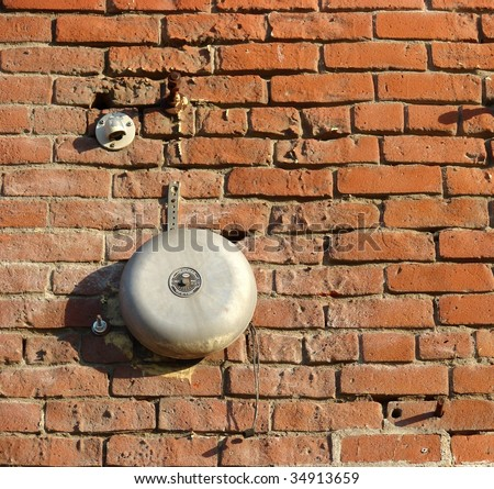 Vintage alarm bell on old brick building