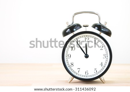 Vintage alarm clock on old wood wall table. /Alarm clock with 5 min before 12 o`clock on old wood table. - stock photo