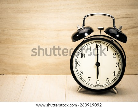 Vintage alarm clock on table. - stock photo