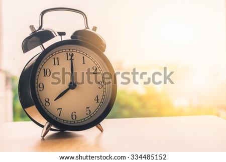 Vintage alarm clock on wood table beside window at mornig time ( alarm clock show 8 o`clock ) - stock photo
