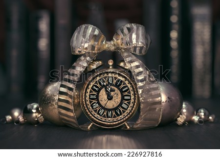 Vintage alarm clock showing five to twelve on the wooden table in study room. Happy New Year 2015! - stock photo