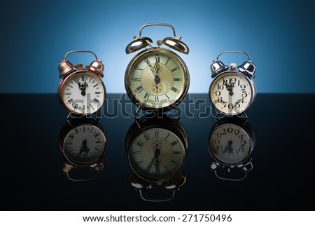 Vintage alarm clocks showing five minutes to twelve, blue background - stock photo