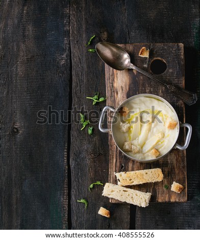 Vintage aluminum pan with white asparagus cream soup with pea sprouts and toast, served on wooden chopping board over old wooden background. Dark rustic style. Flat lay with copy space - stock photo