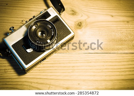 vintage analog camera on a rustic wooden background - stock photo