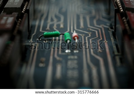 Vintage analog printed circuit board in a dark colors with mounted electronic components. Close up with extremely shallow DOF. - stock photo