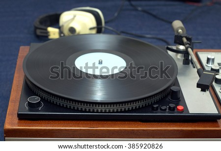 Vintage analogue classic style record player in wooden case with vinyl record and headphones. Horizontal photo front view closeup