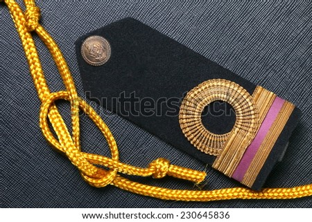Vintage and old Royal Thai Navy arm put beside gold color rope represent Thai navy arm accessory to use with uniform . - stock photo